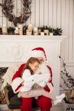Девушка santa праздника рождества счастливая смотря что-то на цифровом ПК таблетки экрана касания, над печной трубой и деревом Стоковые Фото