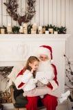 Девушка santa праздника рождества счастливая смотря что-то на цифровом ПК таблетки экрана касания, над печной трубой и деревом Стоковые Фотографии RF