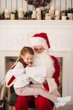 Девушка santa праздника рождества счастливая смотря что-то на цифровом ПК таблетки экрана касания, над печной трубой и деревом Стоковая Фотография