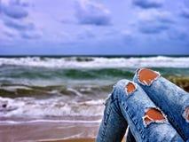 Девушка selfie ноги хот-дога сидя около океана с волнами Стоковые Фотографии RF