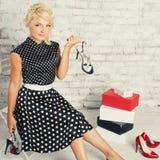 Девушка Shopaholic белокурая в платье сидя с ботинками стоковое изображение rf