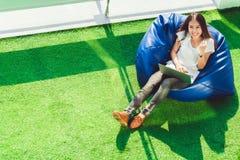 Девушка Sian празднует с компьтер-книжкой тетради, сидит на сумке фасоли в саде Мелкий бизнес успеха, концепция информационной те стоковая фотография