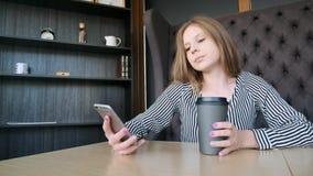 Девушка Smartphone используя app на кофе телефона выпивая усмехаясь в кафе Красивый молодой вскользь женский профессионал на черн сток-видео