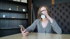 Девушка Smartphone используя app на кофе телефона выпивая усмехаясь в кафе Красивый молодой вскользь женский профессионал на черн видеоматериал