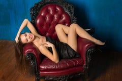 Девушка Smilling красивая лежит в кресле Стоковые Изображения