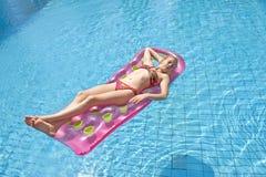 Девушка sunbathing на тюфяке Стоковая Фотография