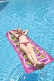 Девушка sunbathing на тюфяке Стоковые Изображения