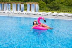 Девушка Tan сидит на раздувных фламинго тюфяка и ослабляет в бассейне стеклянная женщина красного вина бассеина партии удерживани Стоковое Фото