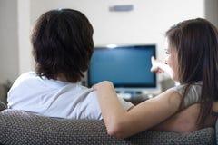 девушка tv мальчика передняя Стоковая Фотография