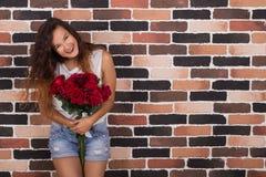 Девушка Yong красивая держа розы и усмехаться Стоковые Изображения