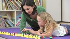Девушке учителя показывающ как подсчитать с пластичными игрушками акции видеоматериалы
