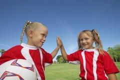 Девушки давая высоко--5 на футбольном поле Стоковая Фотография