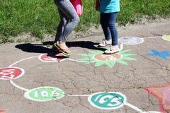 Девушки бегут на ребяческих чертежах на асфальте Стоковое фото RF