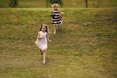 Девушки бегут от холма на зеленой траве на летний день Стоковое Изображение
