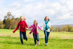 Девушки бежать через парк падения или осени Стоковые Изображения