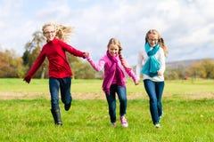 Девушки бежать через парк падения или осени Стоковая Фотография RF