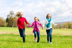 Девушки бежать через парк падения или осени Стоковая Фотография