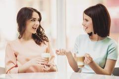 2 девушки беседуя в столовой с чашками кофе Стоковое фото RF