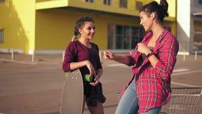 2 девушки битника готовя магазинную тележкау на автостоянке citymall во время захода солнца Девушка в рубашке шотландки сток-видео