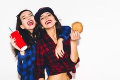 Девушки битника с вегетарианским бургером выпивая соду от соломы и имея потеху, счастливую, усмехаются и смеются над на белизне Стоковое Изображение RF