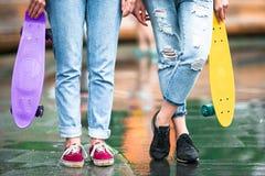 2 девушки битника с скейтбордом outdoors в свете захода солнца Skatebords крупного плана в женских руках Активные sporty женщины Стоковые Фото