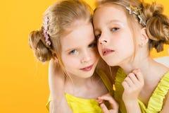 Девушки близнецов сидят на стуле на желтой предпосылке Стоковое Фото