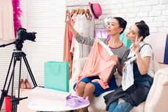 2 девушки блоггера моды задерживают 2 красочных платья к камере принимая selfie Стоковая Фотография