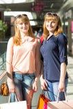 Девушки близнецов детенышей имеют потеху держа их хозяйственные сумки Стоковое Изображение RF