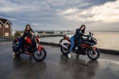2 девушки велосипедиста в кожаных куртках на мотоциклах спорта черного и красного цвета Стоковая Фотография RF