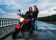 2 девушки велосипедиста в кожаных куртках на мотоцикле спорта черного и красного цвета Стоковое Изображение