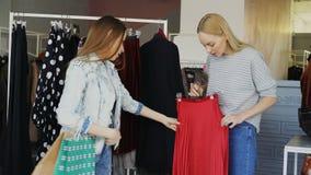 Девушки выбирают одежды пока стоящ близко рельсы в роскошном магазине Они принимают юбку, приспосабливая ее для того чтобы провер сток-видео