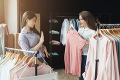 2 девушки выбирая одежды на магазине Стоковое фото RF