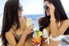 Девушки выпивая коктеили на пляже Стоковая Фотография