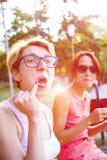 Девушки выпивая кофе в парке Стоковые Изображения