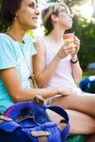 Девушки выпивая кофе в парке Стоковая Фотография