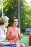 Девушки выпивая кофе в парке Стоковое Фото