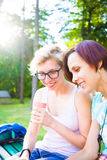 Девушки выпивая кофе в парке Стоковое Изображение