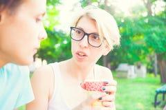 Девушки выпивая кофе в парке Стоковая Фотография RF