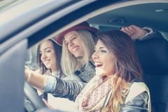 3 девушки в автомобиле Девушки могут управлять автомобилем через город Стоковые Изображения