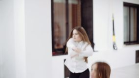 2 девушки в белых блузках и черных брюках танцуют перед зеркалом акции видеоматериалы