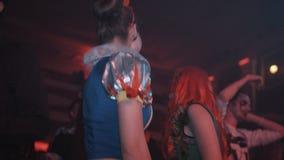 Девушки в белизне снега и костюмы плюща отравы танцуют на партии хеллоуина ночного клуба акции видеоматериалы