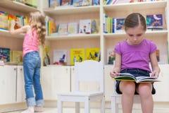 Девушки в библиотеке решили прочитать книгу Стоковые Изображения