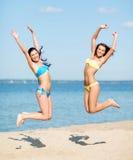 Девушки в бикини скача на пляж Стоковые Изображения