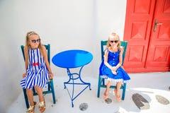 2 девушки в голубых платьях сидя в внешнем кафе на улице типичной греческой деревни на острове Mykonos, Греции Стоковое Изображение RF