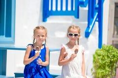 2 девушки в голубых платьях сидя на голубых стульях и таблице на улице типичной греческой традиционной деревни с белизной Стоковые Фото