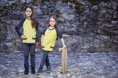 2 девушки в желтом скейтборде владением одежд Стоковое Изображение
