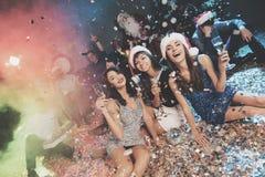 3 девушки в красивых платьях вечера сидят на поле с стеклами шампанского в их руках Стоковое Изображение RF