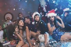 3 девушки в красивых платьях вечера сидят на поле с стеклами шампанского в их руках Стоковые Фото
