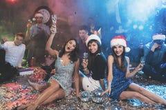 3 девушки в красивых платьях вечера сидят на поле с стеклами шампанского в их руках Стоковое Фото