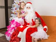 Девушки в красивых платьях обнимают Санта Клауса сидя на кресле Стоковая Фотография